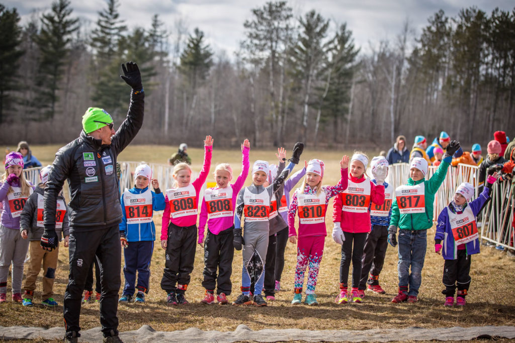 Brian Gregg of Team Gregg leading warm-ups before the Junior and BarneBirkie running races. Not much snow but lots of enthusiastic kids! [Photo] Courtesy of ©American Birkebeiner Ski Foundation. [Photo] Courtesy of ©American Birkebeiner Ski Foundation