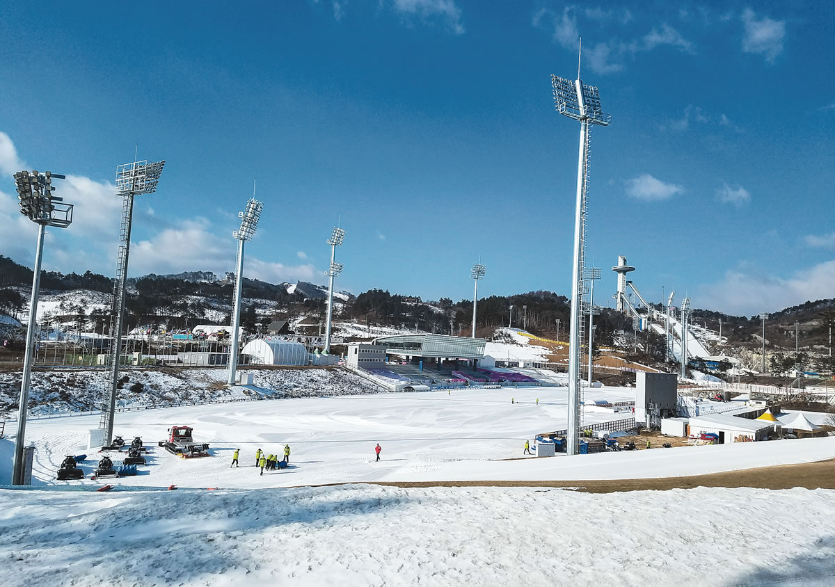 Moving snow and laying tracks. Officials prep the venue before a World Cup test event. [Photo] Jason Kask